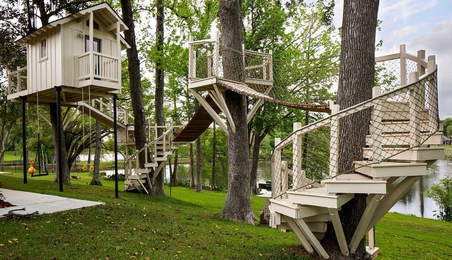 White treehouse with ladder bridge